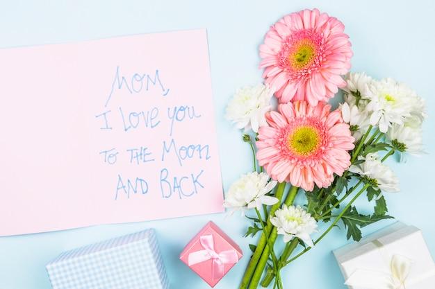 Buquê de flores frescas perto de papel com palavras e caixas de presentes Foto gratuita