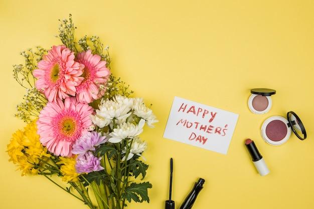 Buquê de flores frescas perto de papel com palavras felizes dia das mães e batons com pós Foto gratuita