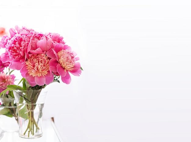 Buquê de flores lindas peônia fresca em um vaso de vidro transparente, sobre um fundo branco Foto gratuita