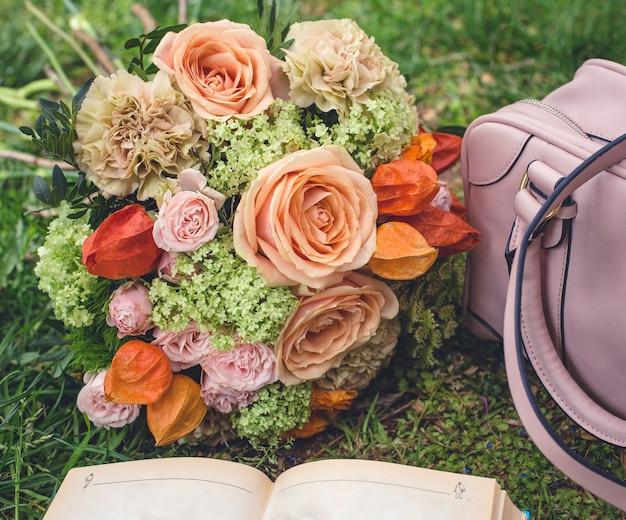 Buquê de flores na grama, sacola e um livro Foto gratuita