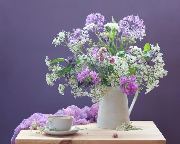 Buquê de flores. natureza morta com jardim e flores silvestres em um jarro e um par de chá em uma tabela Foto Premium
