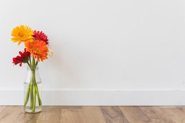 Buquê de flores no vaso perto da parede Foto gratuita