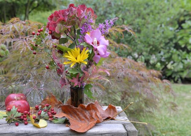 Buquê de flores outonais provenientes de jardim em uma mesa de jardim com maçãs e folhas Foto Premium