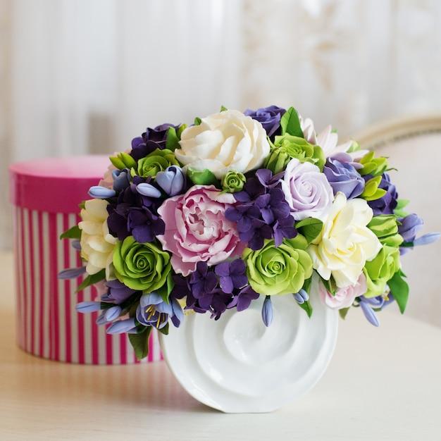 Buquê de flores rosa e caixa de presente na mesa de madeira Foto Premium