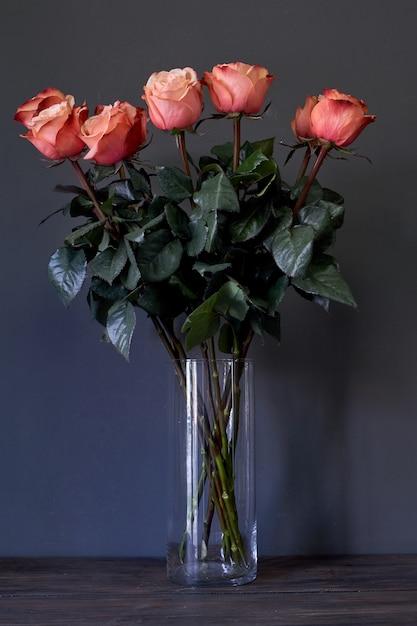 Buquê de flores rosas em um vaso de cristal alto claro contra uma parede cinza, foco seletivo Foto Premium