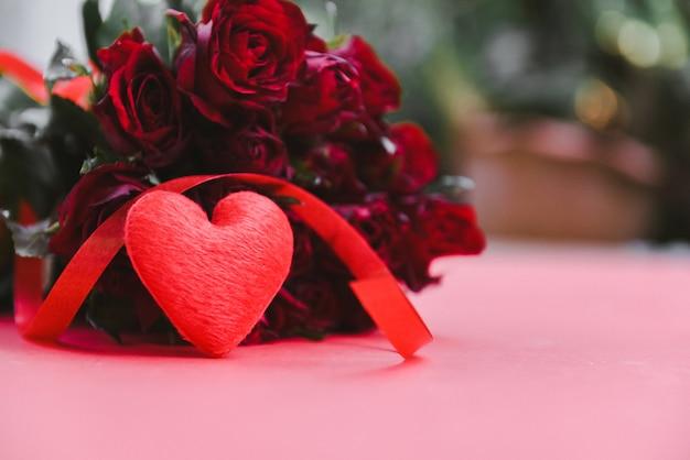 Buquê de flores rosas em vermelho. coração vermelho com fita e rosa conceito de dia dos namorados amor romântico Foto Premium