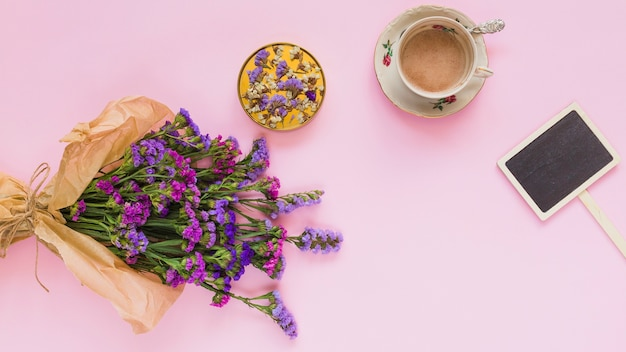 Buquê de flores roxas; montanha russa; xícara de café; e rótulo de cartaz no fundo rosa Foto gratuita