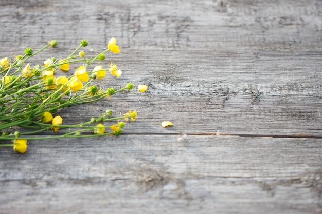 Buquê de flores silvestres amarelas sobre um fundo de madeira velha, com um lugar sob a inscrição, a vista do arranjo floral superior Foto Premium
