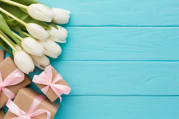 Buquê de flores tulipa com presentes em fundo de madeira Foto gratuita