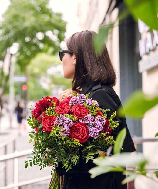 Buquê de flores variuos nas mãos da menina Foto gratuita