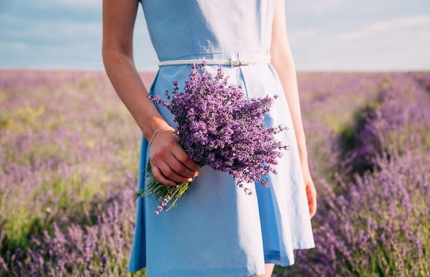 Buquê de lavanda nas mãos de uma menina em um vestido azul Foto Premium