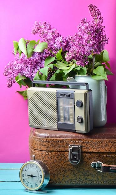 Buquê de lilases na chaleira esmaltada na mala antiga, rádio vintage, despertador em fundo rosa. estilo retro ainda vida Foto Premium