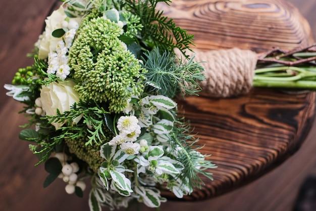 Buque de noiva. casamento. buquê de flores brancas e verdes fica em uma cadeira contra Foto Premium
