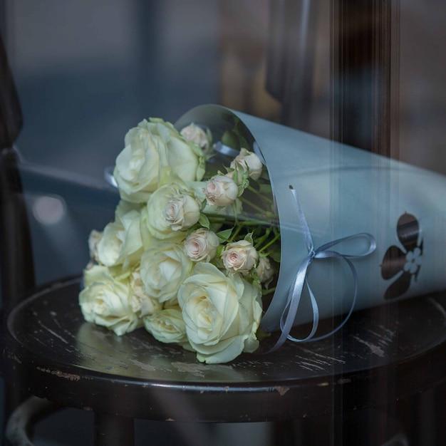Buquê de papel cinza de rosas brancas em pé em uma cadeira de madeira preta Foto gratuita
