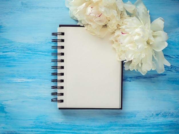 Buquê de peônias brancas, desabrochando e uma página de bloco de notas em branco Foto Premium