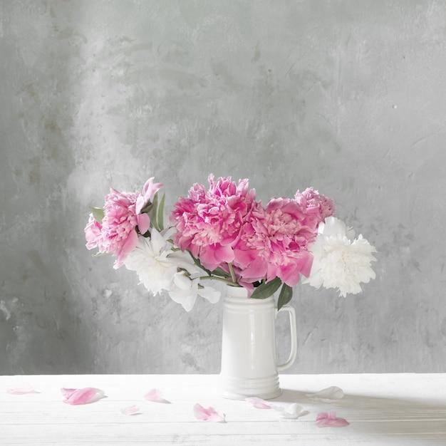 Buquê de peônias rosa e brancas na parede do fundo antigo Foto Premium