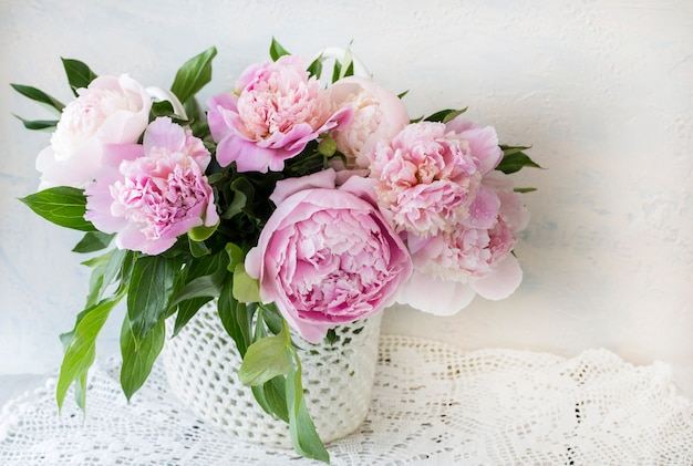 Buquê de peônias rosa em uma mesa de madeira em uma cesta artesanal na toalha de mesa de renda Foto Premium