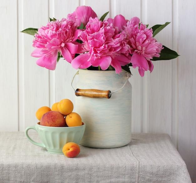 Buquê de peônias rosa, pêssegos e damascos na mesa. Foto Premium
