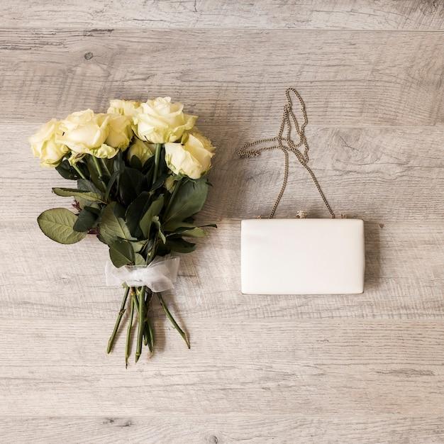 Buquê de rosas amarrado com fita branca com embreagem no pano de fundo de madeira Foto gratuita