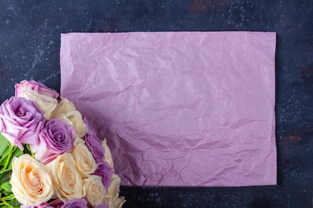 Buquê de rosas brancas e roxas surpreendentes frescas e folha de papel kraft em fundo escuro. Foto Premium