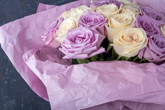 Buquê de rosas brancas e roxas surpreendentes frescas em papel ofício em fundo branco Foto Premium