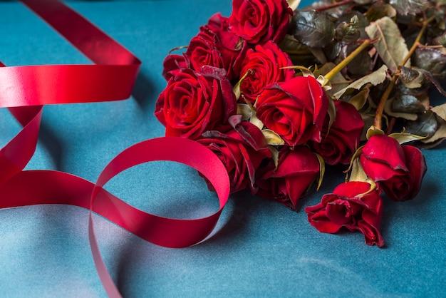 Buquê de rosas com fita vermelha na mesa Foto gratuita