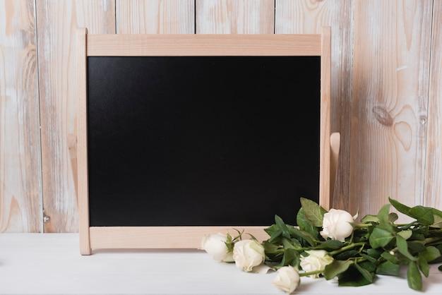 Buquê de rosas com pequena lousa de madeira na mesa branca Foto gratuita