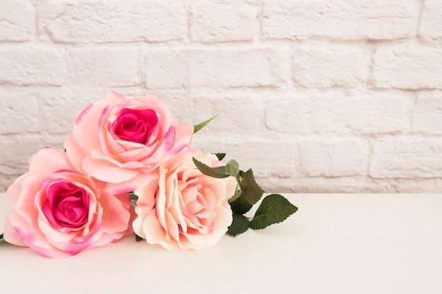 Buquê de rosas em uma mesa branca Foto Premium