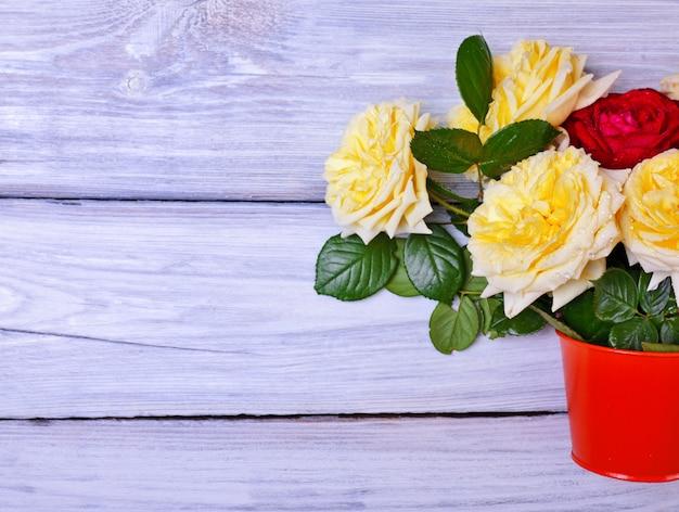 Buquê de rosas florescendo em um balde de laranja Foto Premium