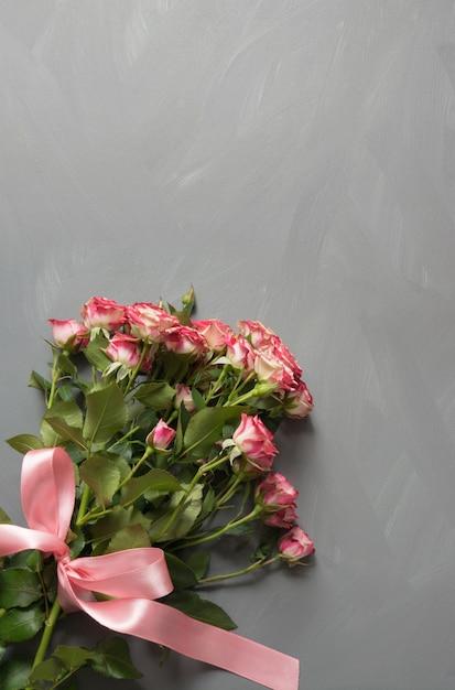 Buquê de rosas rosa com laço rosa em cinza Foto Premium