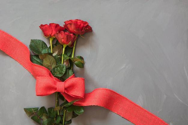 Buquê de rosas vermelhas e fita vermelha na cinza Foto Premium