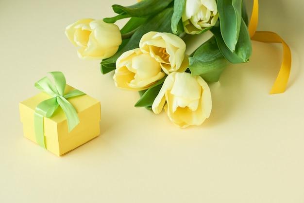 Buquê de tulipas amarelas com caixa de presente na luz Foto Premium