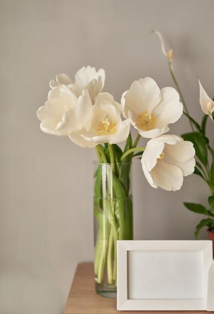 Buquê de tulipas brancas e molduras vazias. Foto Premium