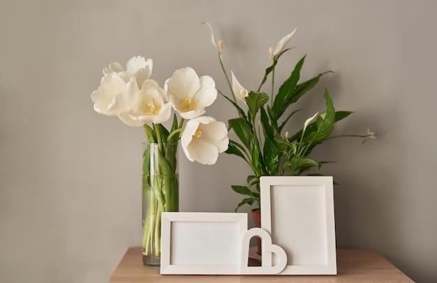 Buquê de tulipas brancas frescas e molduras vazias. Foto Premium