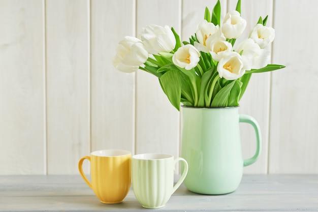 Buquê de tulipas brancas frescas em vaso e duas canecas Foto Premium