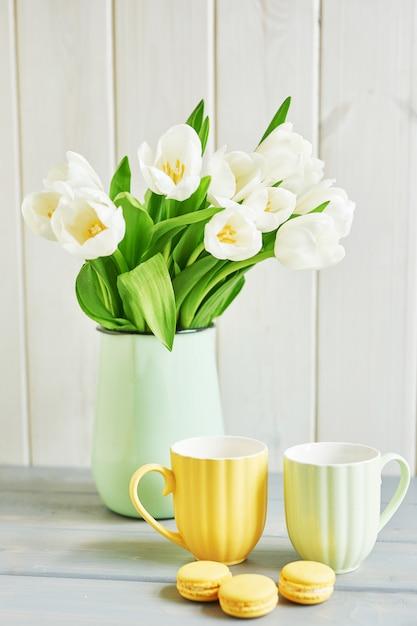 Buquê de tulipas brancas frescas em vaso, macarons de limão e duas canecas Foto Premium