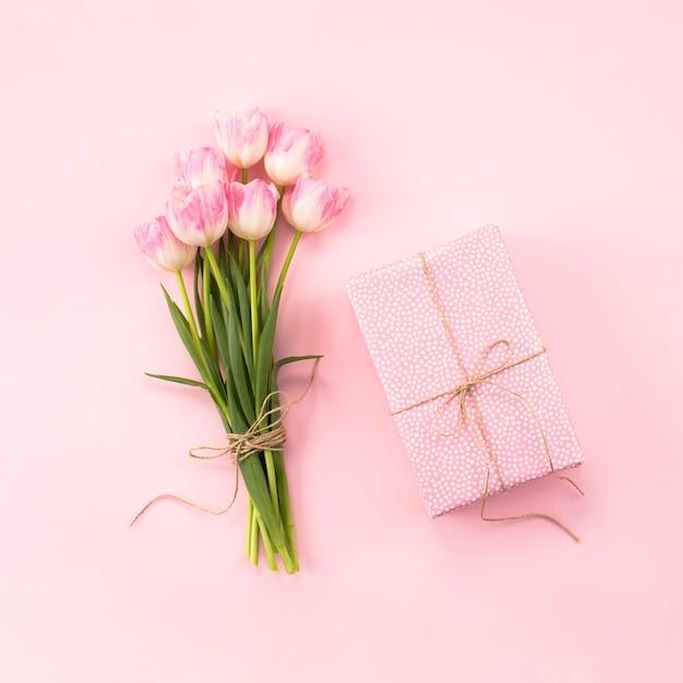 Buquê de tulipas com caixa de presente na mesa Foto gratuita