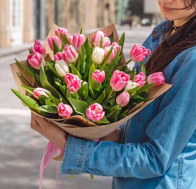 Buquê de tulipas cor de rosa nas mãos da menina Foto gratuita