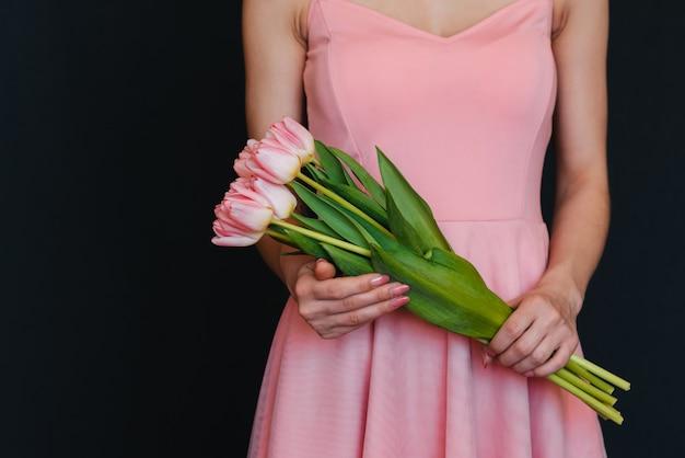 Buquê de tulipas cor de rosa nas mãos das mulheres Foto Premium