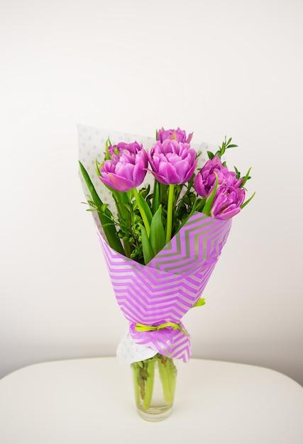 Buquê de tulipas exuberantes violetas lindas em um vaso Foto Premium