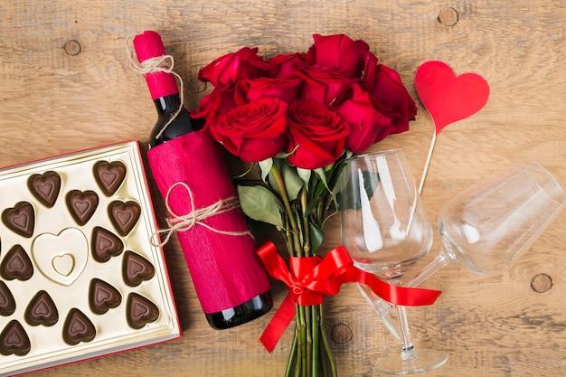 Buquê de vista superior de rosas e vinho saboroso Foto gratuita