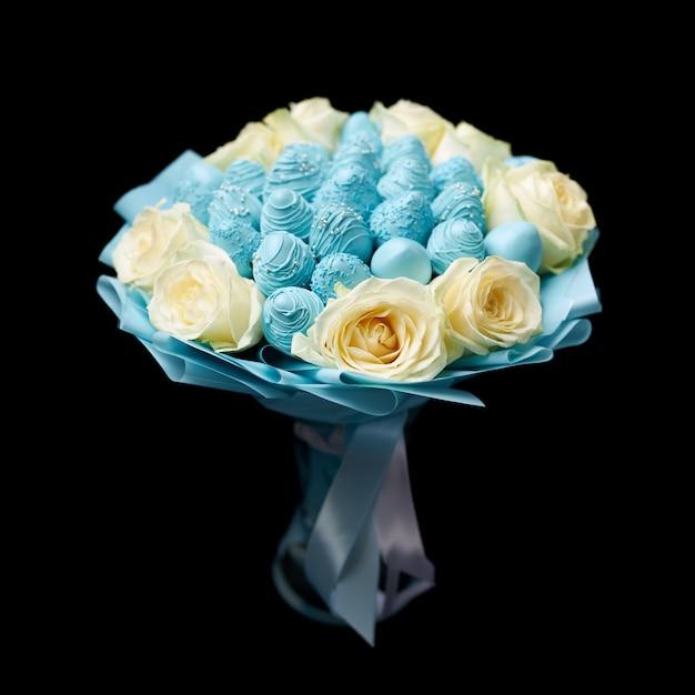 Buquê exclusivo de rosas brancas e morangos maduros cobertos com chocolate azul fica em um vaso em um fundo preto Foto Premium