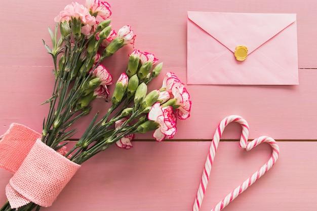 Buquê fresco de flores com fita perto de envelope e bastões de doces Foto gratuita