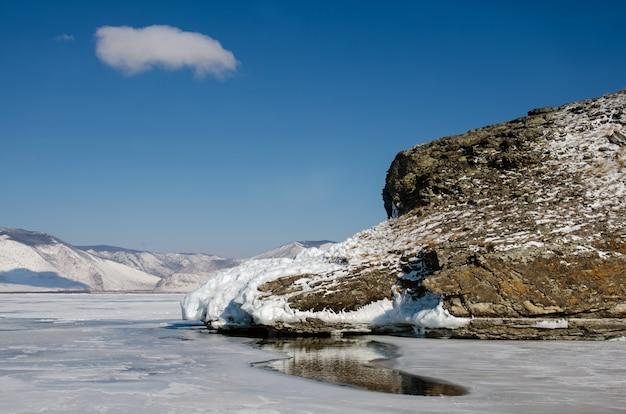 Buraco no gelo do lago baikal com mais de um metro de espessura perto da rocha Foto Premium