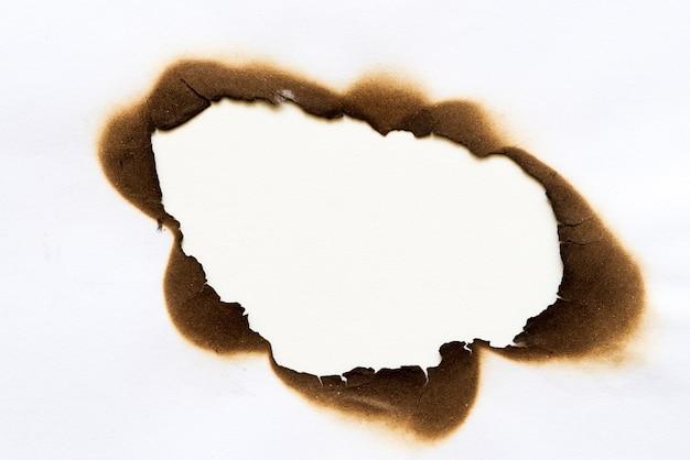 Buraco queimado em pedaço de papel isolado no fundo branco Foto Premium