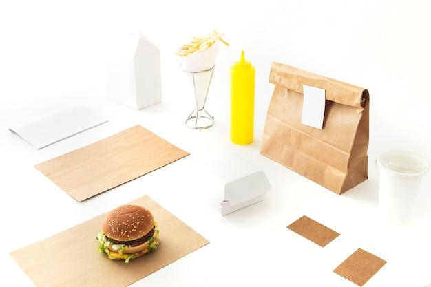 Burger; batatas fritas; pacote de molho e papel no pano de fundo branco Foto gratuita