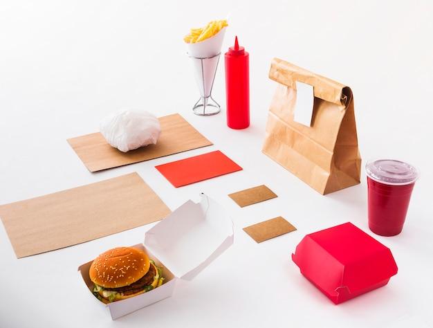 Burger; copo de eliminação; garrafa de molho; batatas fritas e pacote de comida no fundo branco Foto gratuita
