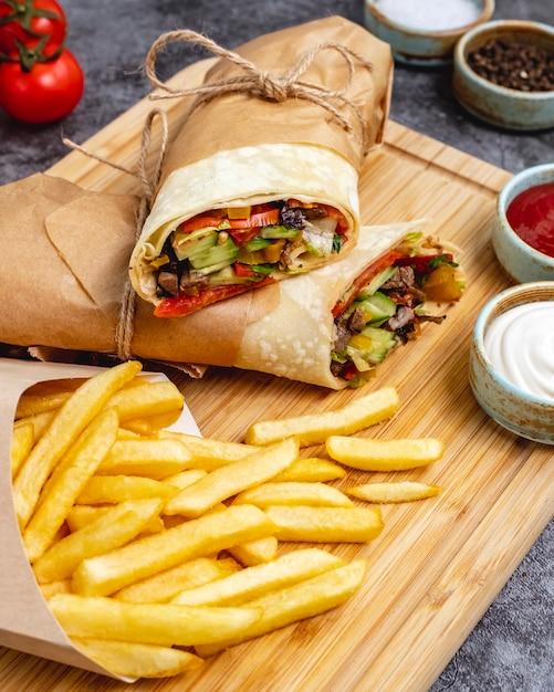 Burrito de carne com jalapeno de alface pepino tomate servido com batatas fritas e molhos verticais Foto gratuita