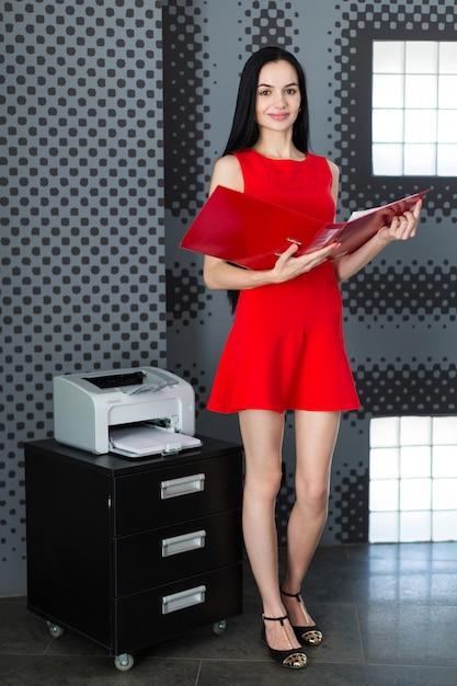 Businesslady atraente vestido vermelho e óculos ficar perto da impressora e mantenha a pasta de papel Foto Premium