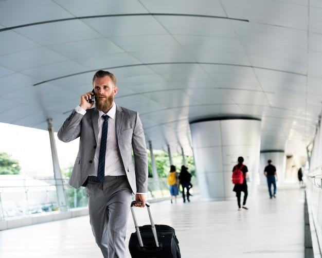 Businessmen walk call phone viagem de negócios de bagagem Foto gratuita